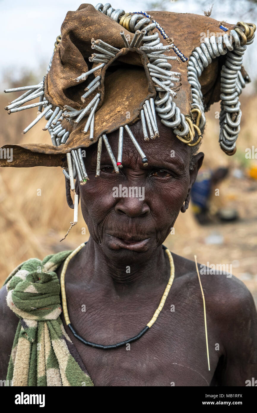 OMORATE, ETHIOPIA - JANUARY 24, 2018: Woman of the Mursi tribe with traditional jewelry with the typical houses of the Mursi in Ethiopia. - Stock Image