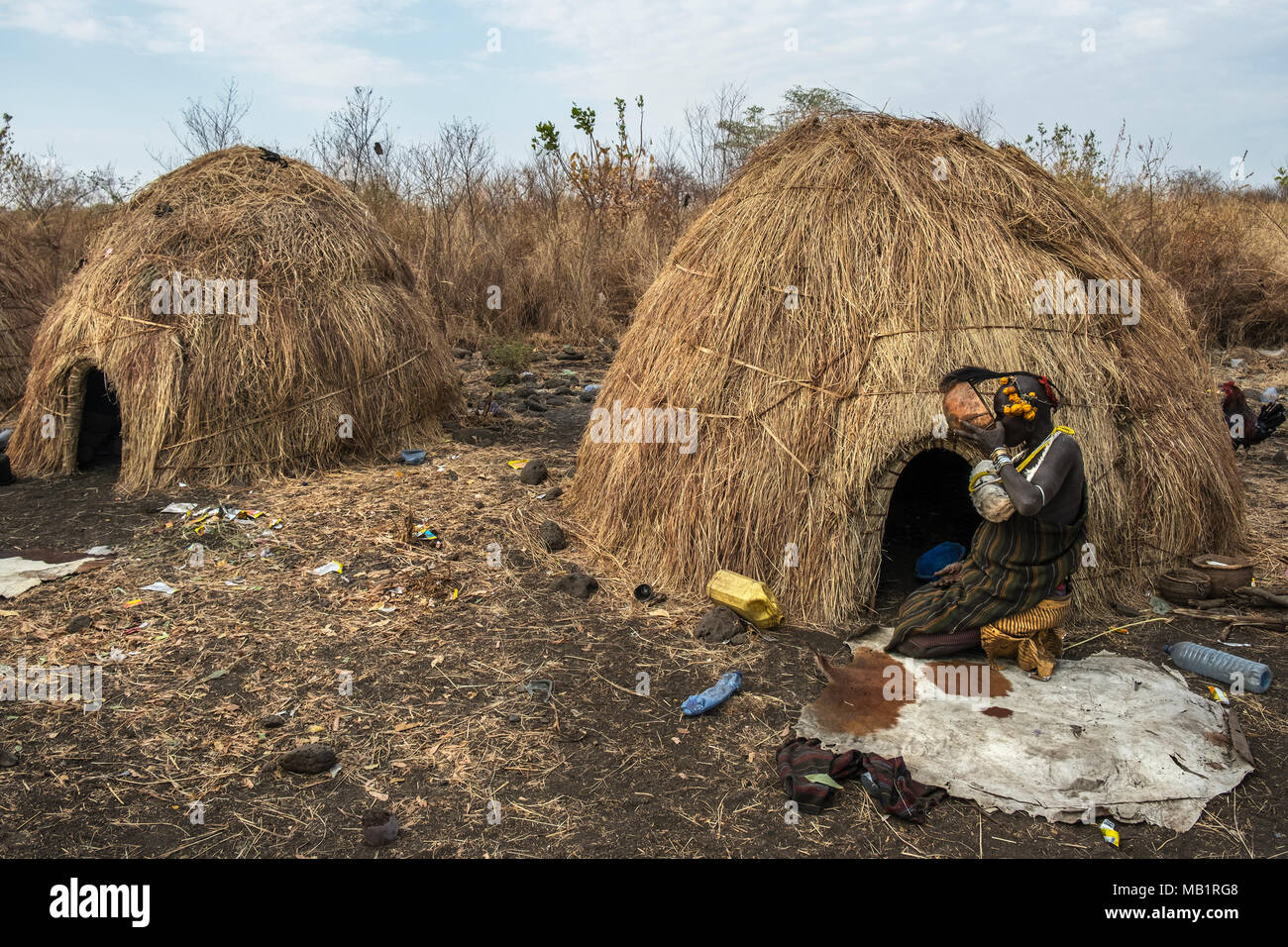 Omorate, Ethiopia - January 24, 2018: Woman of the Mursi tribe drinking in a bowl next to her house in a traditional village of the Mursi in Ethiopia. - Stock Image