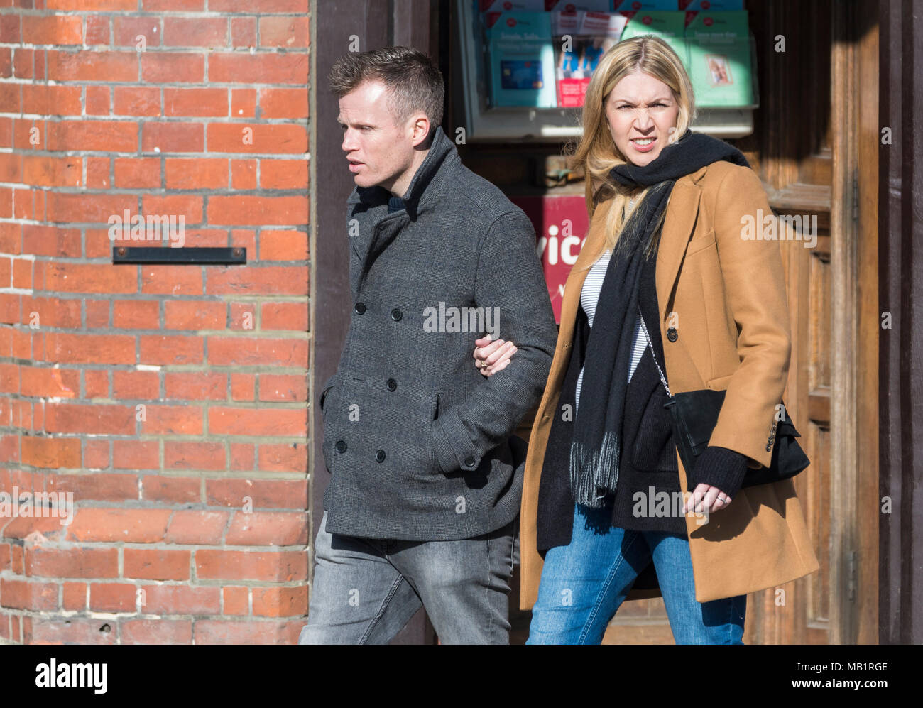 Young couple walking in town with linked arms in the UK. - Stock Image