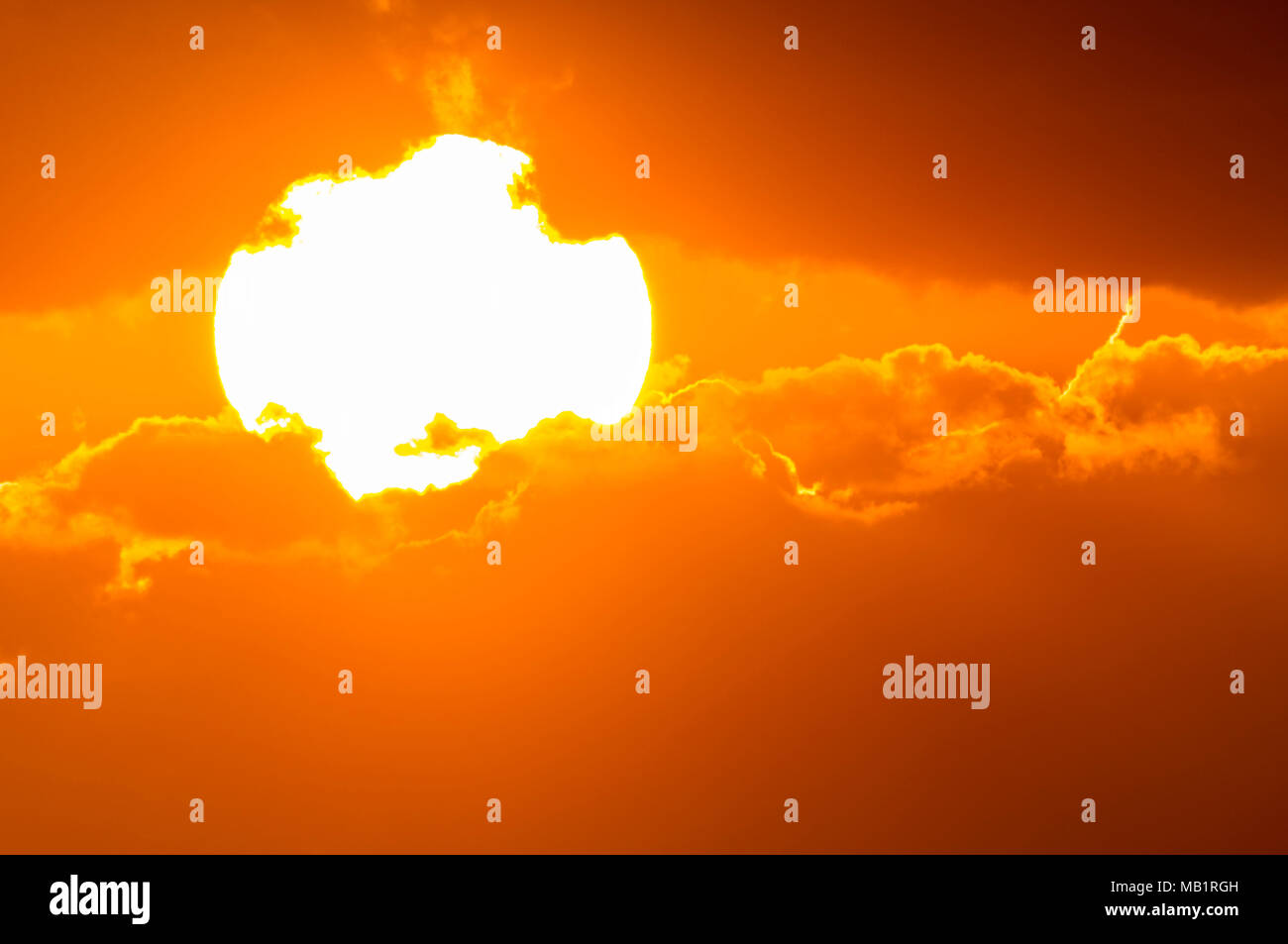Closeup of the glowing bright sun, low in the sky, partially covered by clouds just before it sets. - Stock Image