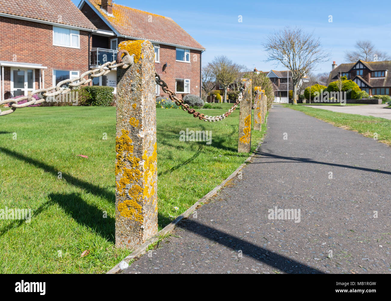 Post and chain low security fence at the end of a front garden with concrete posts covered in moss, by a pavement in England, UK - Stock Image