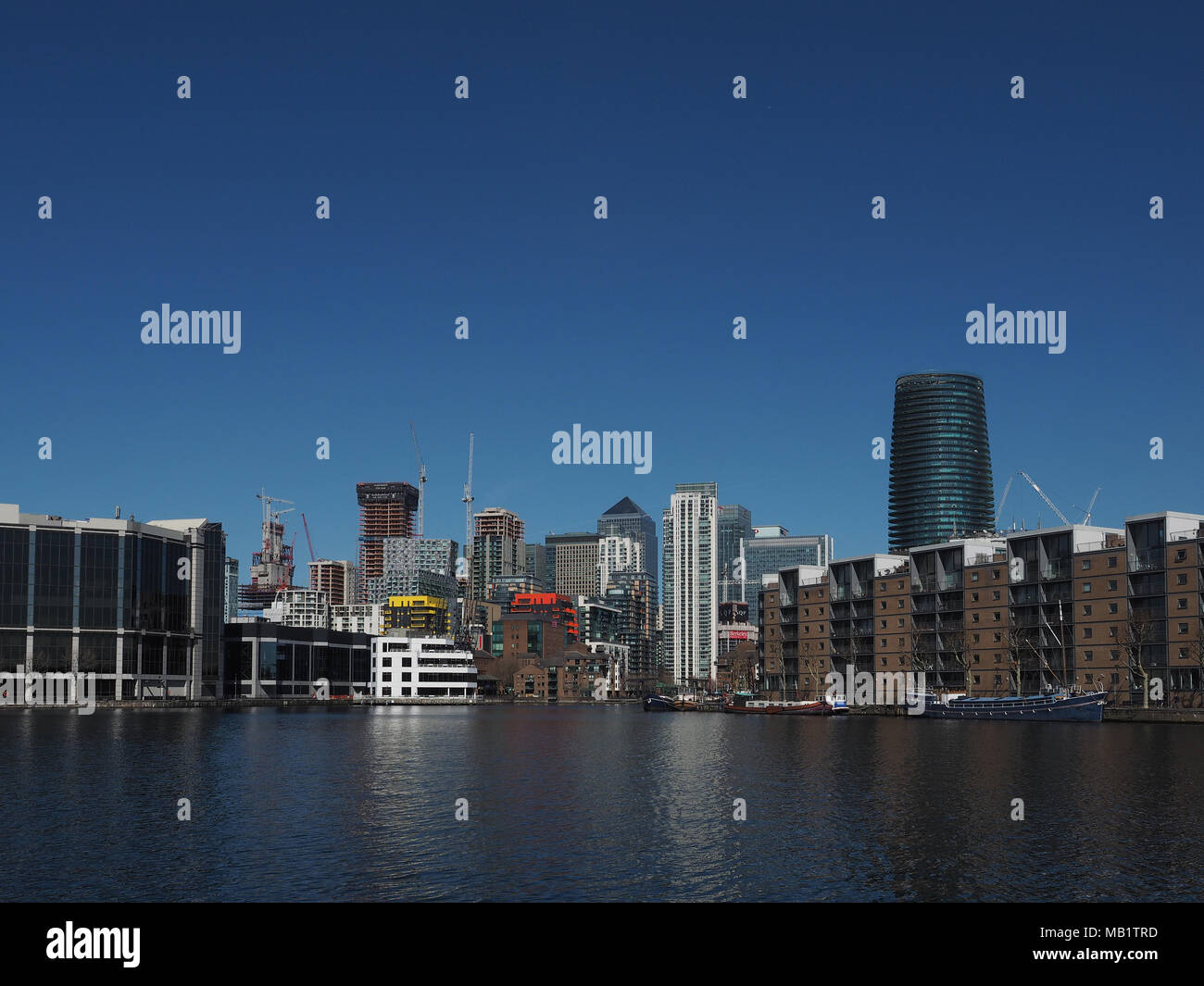Canary Wharf on its construction sites seen from Millwall Outer Dock, London, England, UK - Stock Image