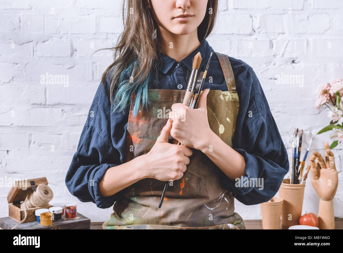cropped image of female artist holding brushes  - Stock Image