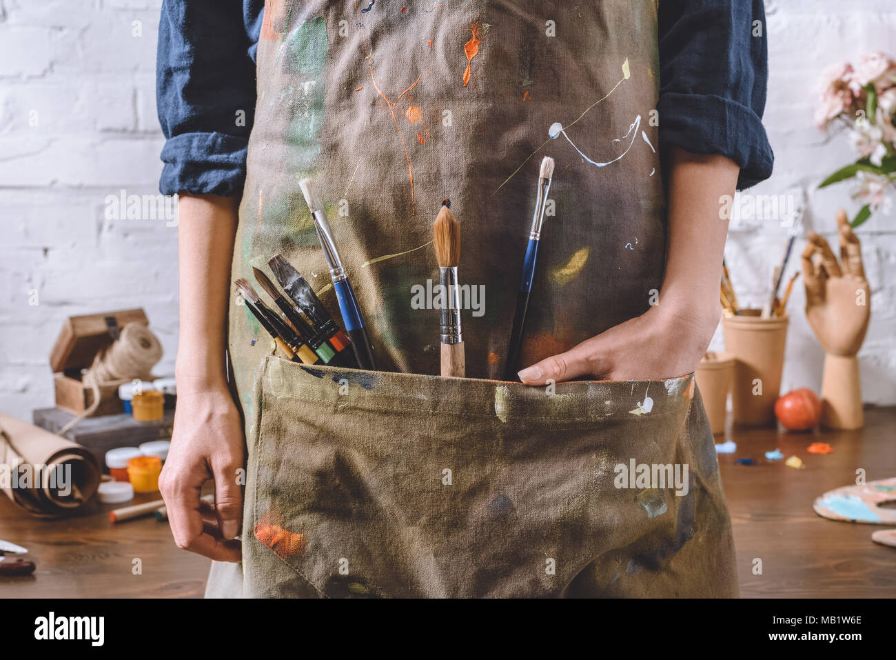 cropped image of artist with brushes and hand in apron pocket - Stock Image