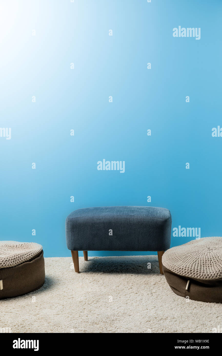 comfy hassocks in front of blue wall - Stock Image