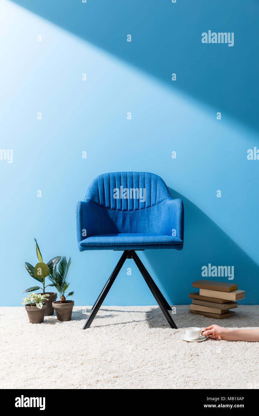 comfy blue armchair with person holding cup of coffee on floor in front of blue wall - Stock Image