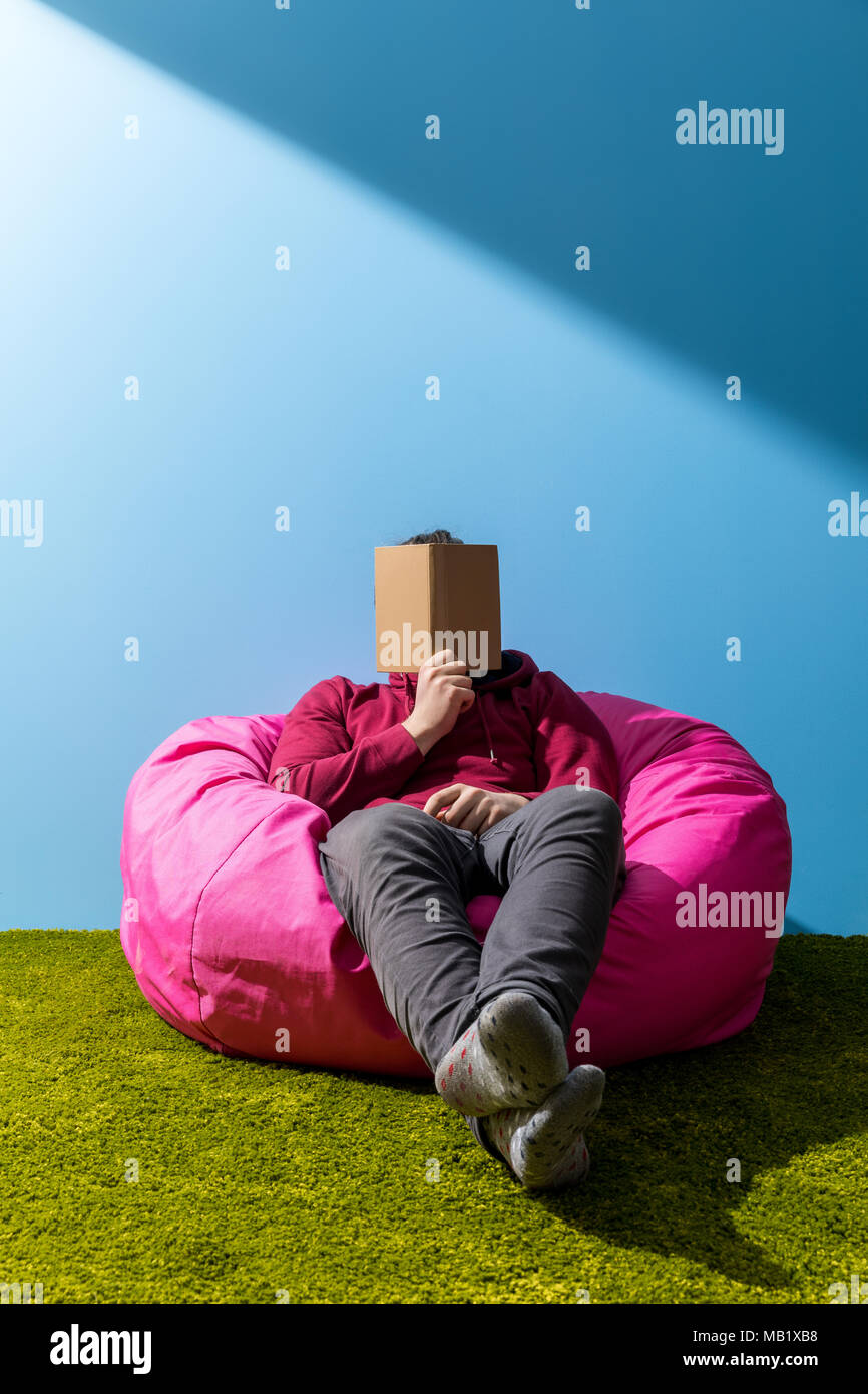 man reading book in bean bag in front of blue wall - Stock Image