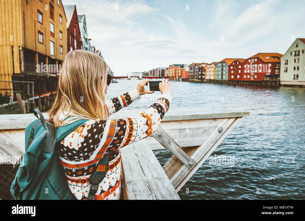 Tourist woman taking photo by smartphone sightseeing in Norway Lifestyle vacations outdoor scandinavian colorful houses landmarks Trondheim city  arch - Stock Image