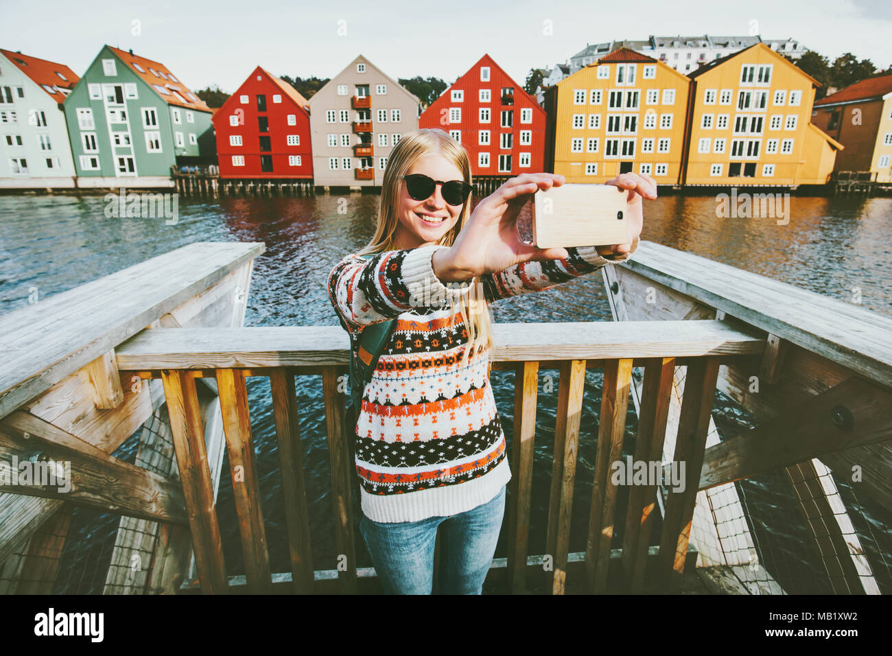 Happy smiling woman taking selfie  traveling in Trondheim city Norway vacations weekend Lifestyle fashion outdoor scandinavian houses landmarks archit - Stock Image