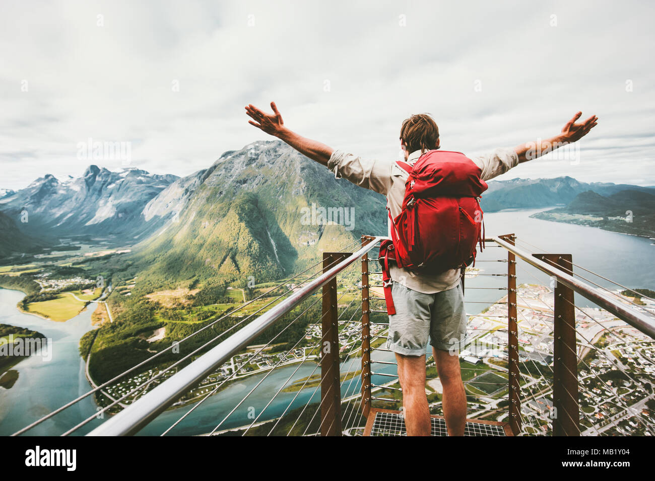 Happy man raised hands enjoying aerial mountains landscape Travel Lifestyle adventure vacations success emotions in Norway traveler with backpack stan - Stock Image