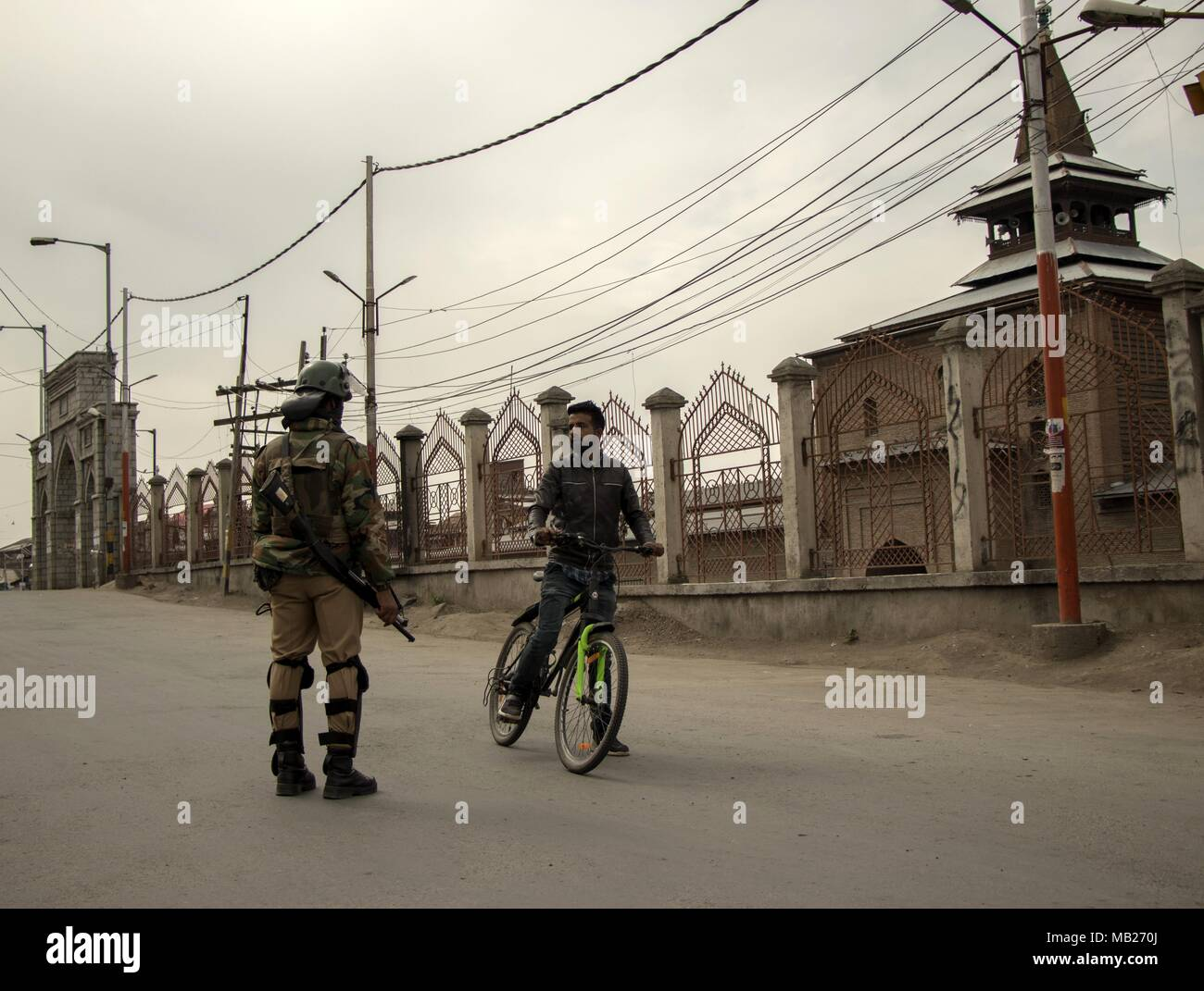 Kashmir, Kashmir. 6th Apr, 2018. An Indian paramilitary trooper stops a cyclist outside Grand Mosque in Downtown area during restrictions in Srinagar city, the summer capital of Kashmir, April 6, 2018. Authorities imposed restrictions in parts of Srinagar city to prevent protests. Credit: Javed Dar/Xinhua/Alamy Live News - Stock Image