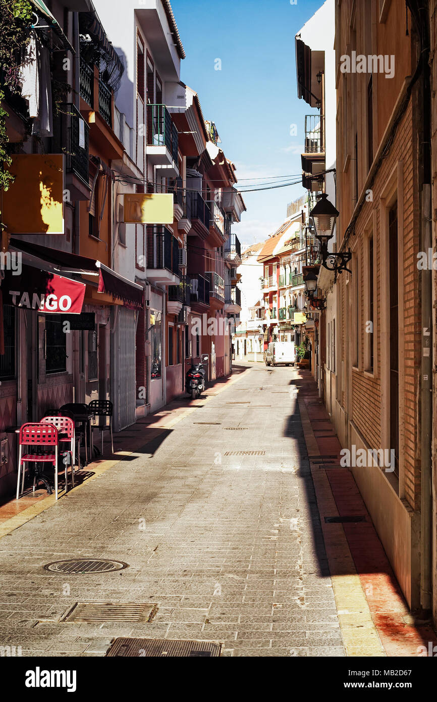 A small tavern is advertizing tango on a narrow alley in Fuengirola, Spain. The town is bathing in the midday sun. - Stock Image
