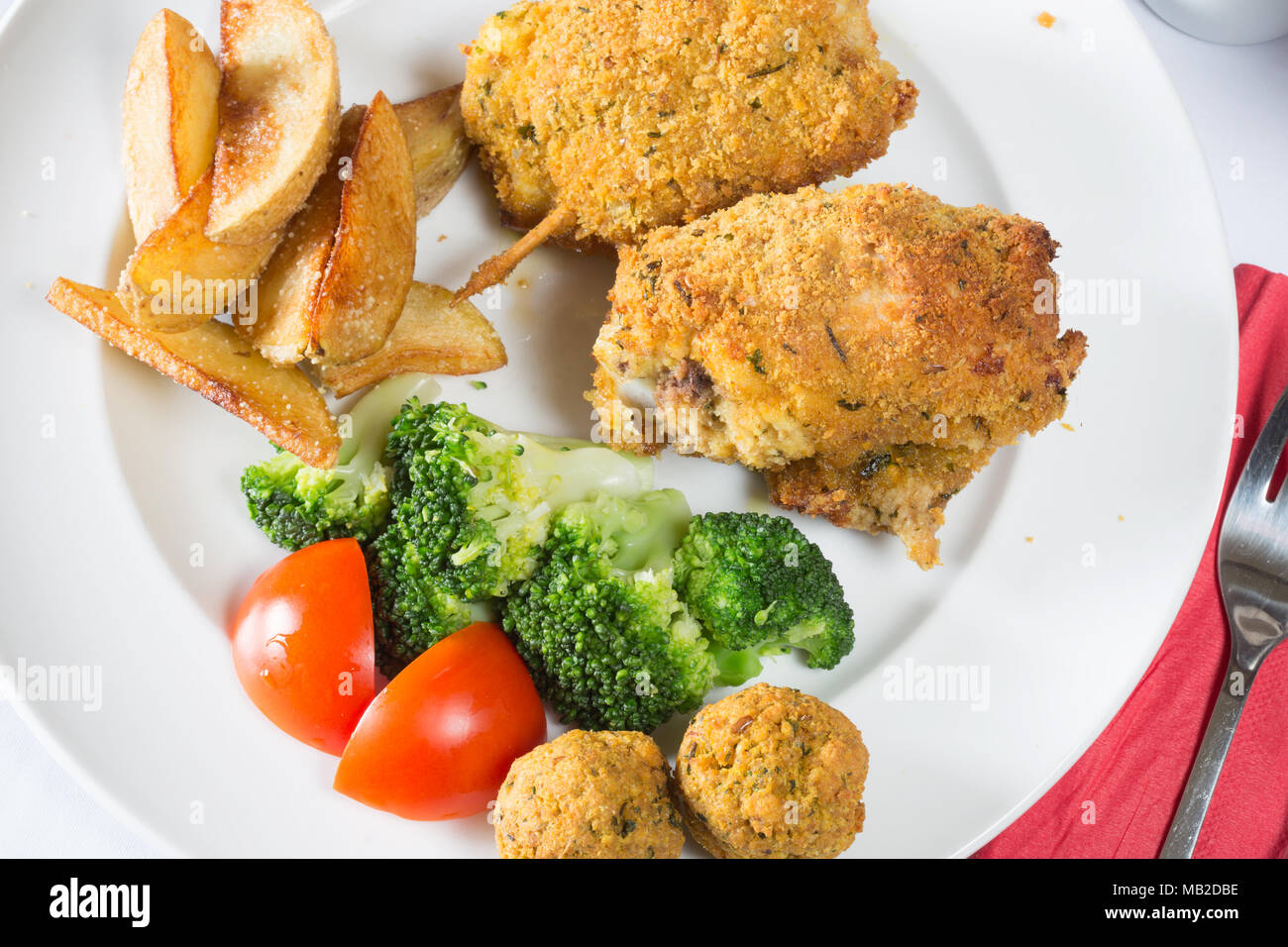 An English pub/restaurant dish of Golden fried breaded Chicken thighs served with potato wedges, Broccoli and stuffing balls - Stock Image