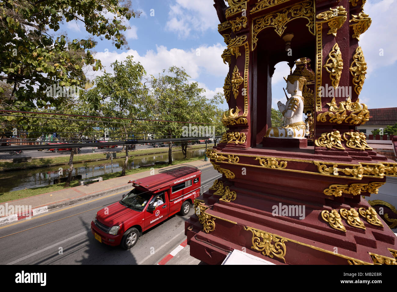 red songthaew taxi driving by a Buddhist temple Wat, Chiang Mai, Thailand - Stock Image
