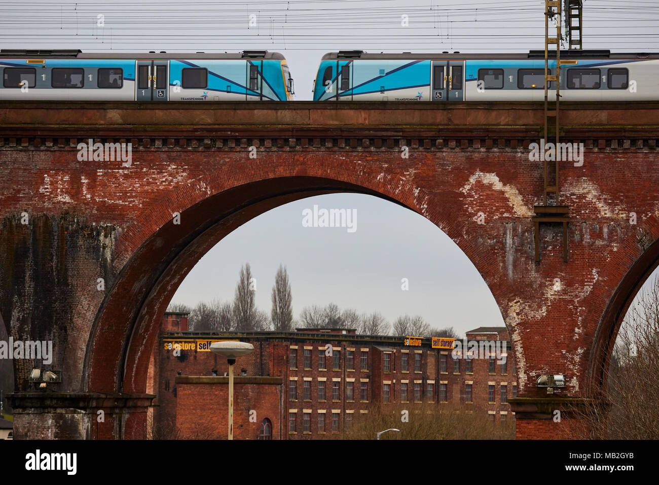 Stockport in Cheshire Gtr Manchester a TransPennine Express operating company owned by FirstGroup franchise. train crossing the landmark brick viaduct - Stock Image