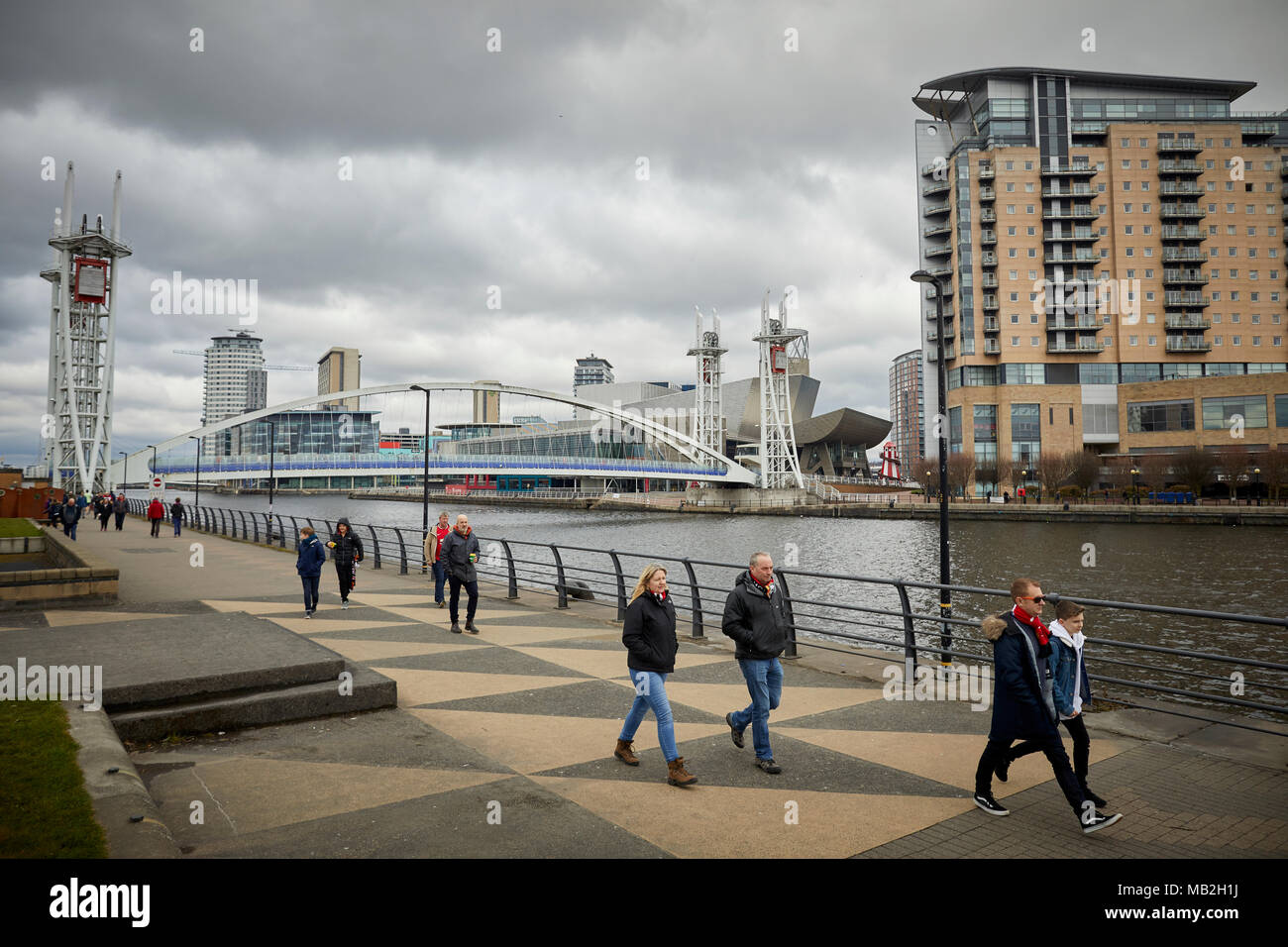 Manchester Ship Canal at Trafford Park Salford Quays, Manchester United football fans walking along the Trafford side to the match - Stock Image