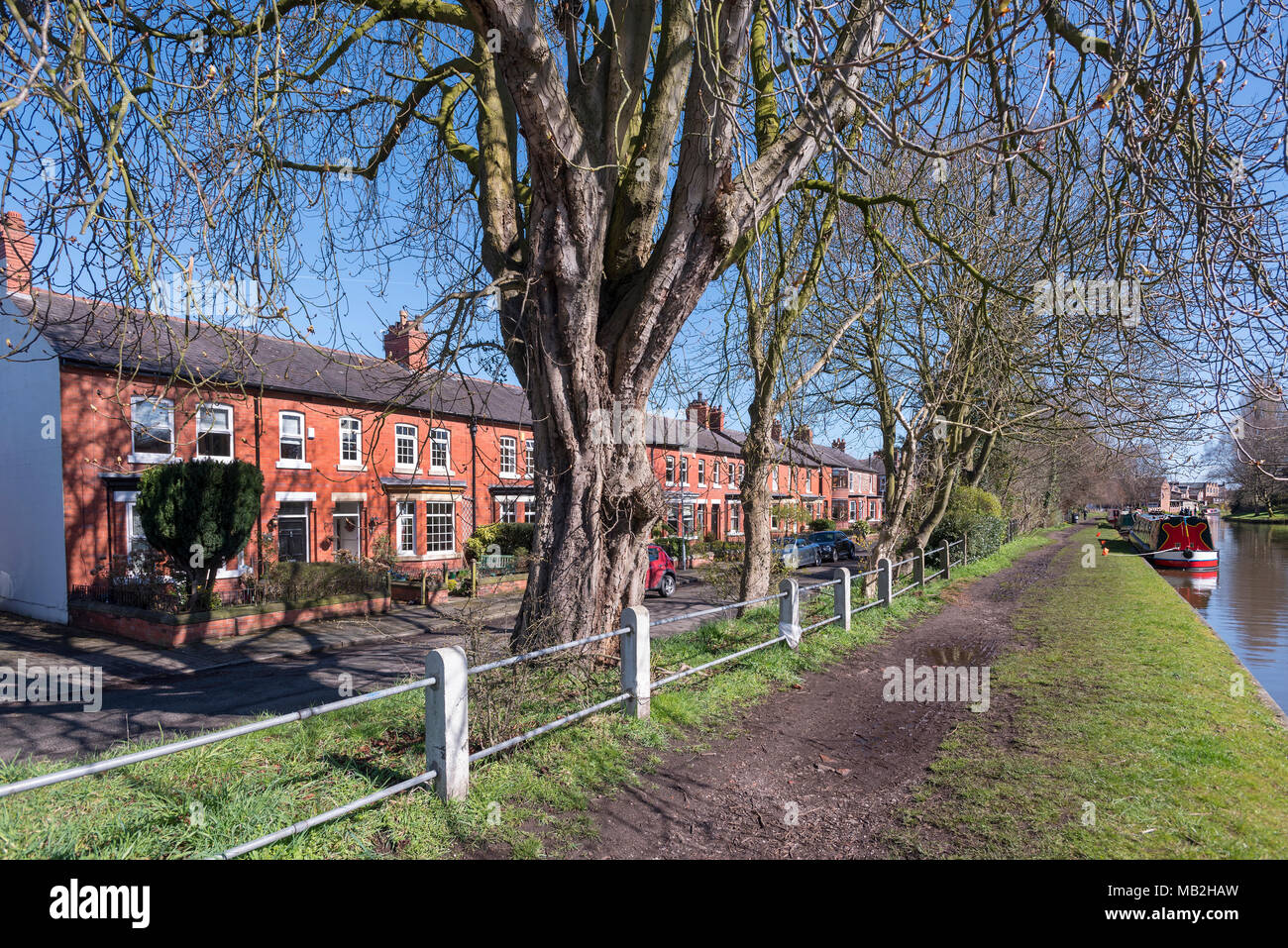 Urban canal towpath scenet on Bridgewater canal at Stockton Heath. Warrington with row of terraced houses - Stock Image