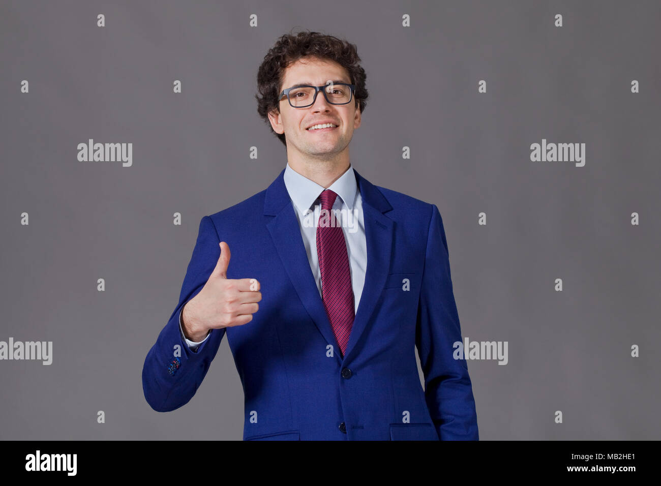 Curly-headed boy smiling and showing big thumb up - Stock Image