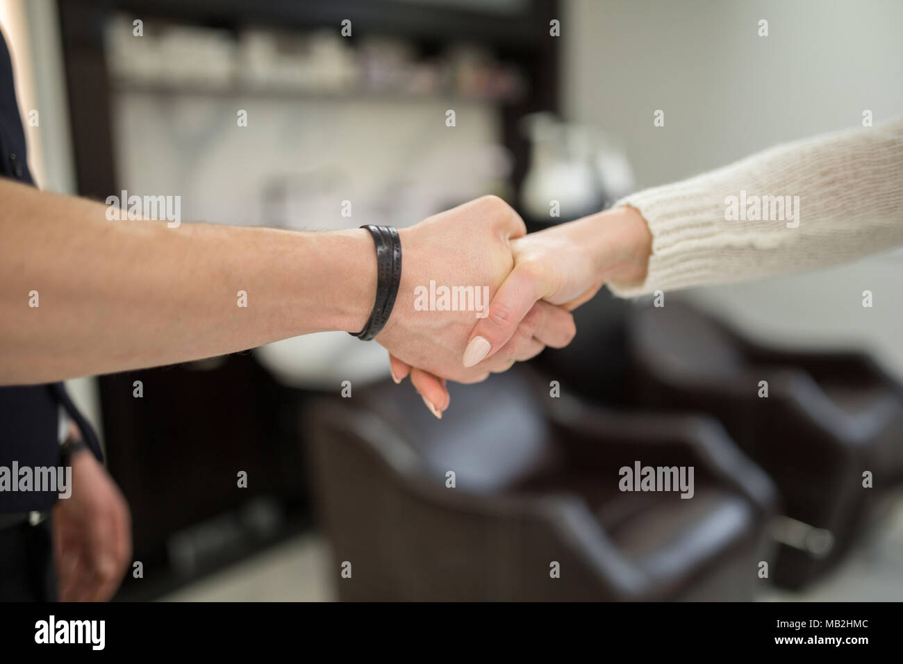 Cropped portrait of people shaking hands at hairdresser salon - Stock Image