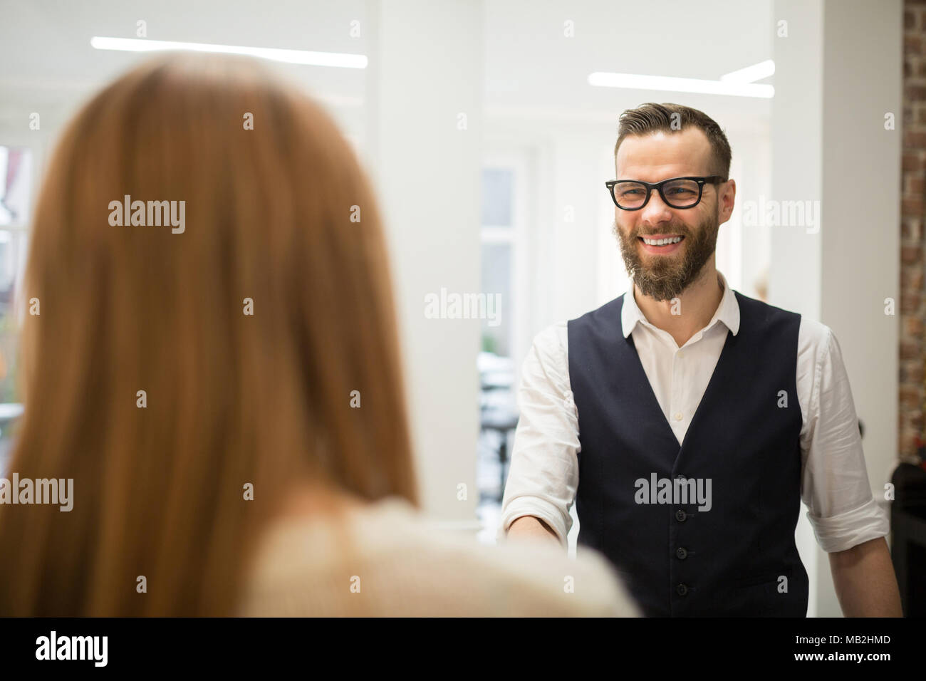 Portrait of happy hairdresser greeting customer at door - Stock Image