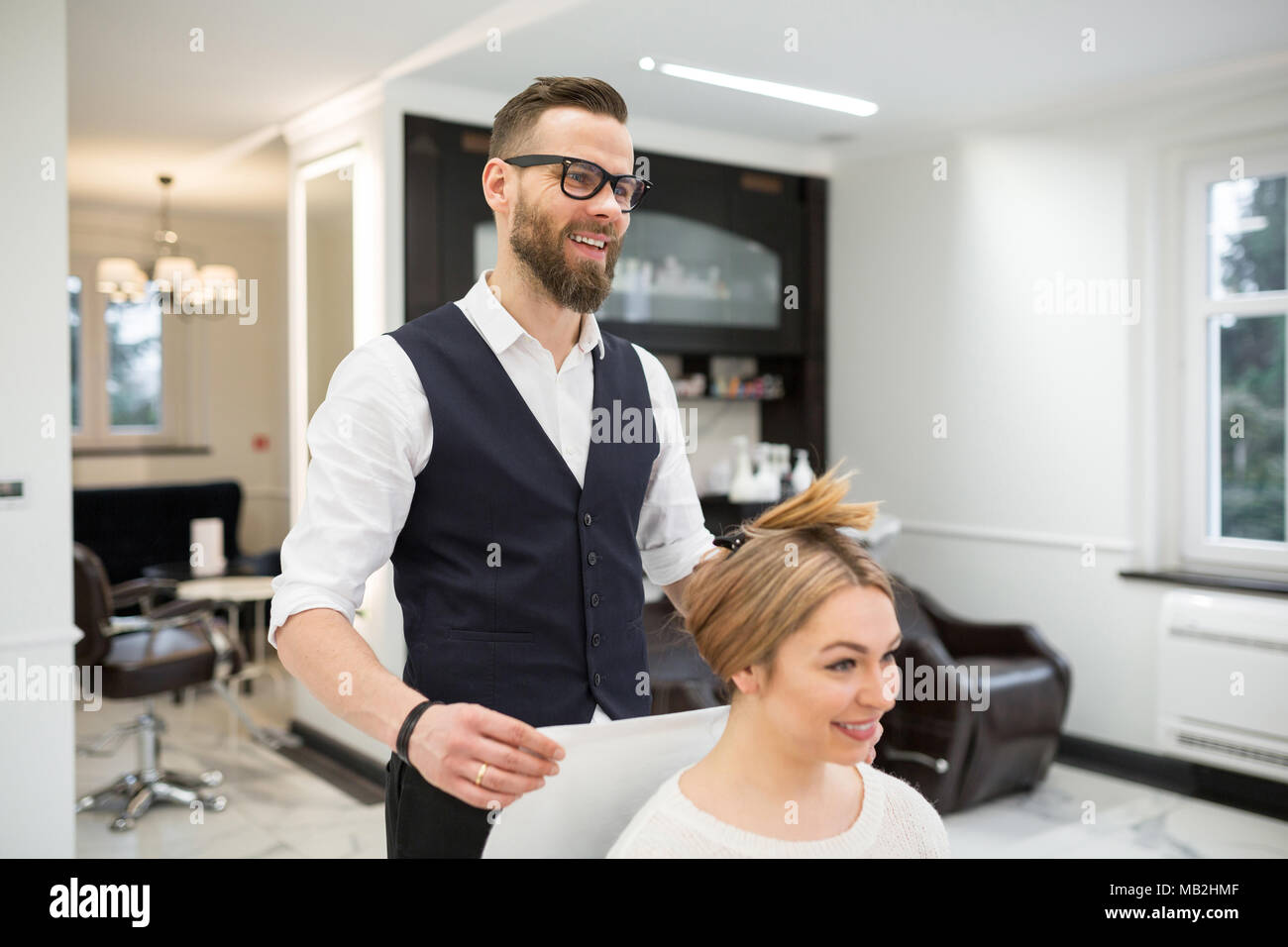 Portrait of happy hairdresser putting towel on client arms - Stock Image