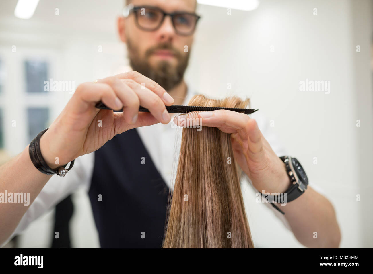 Cropped portrait of hairdresser combing client hair - Stock Image