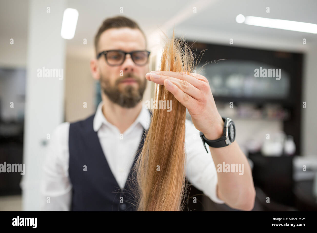 Portrait of focused hairdresser looking at client hair strand - Stock Image