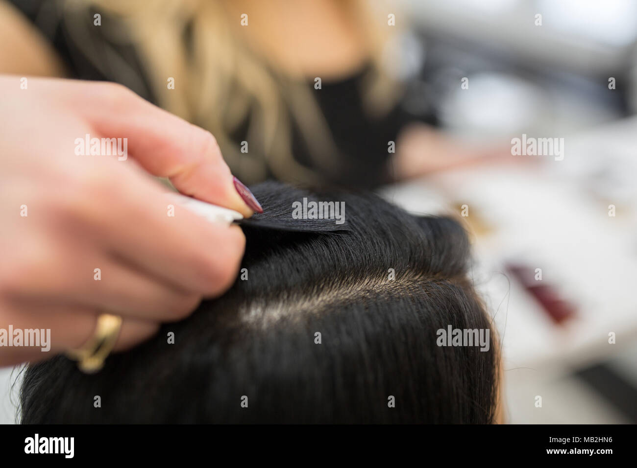 Close up portrait of hairdresser hand putting hair color sample to client head - Stock Image