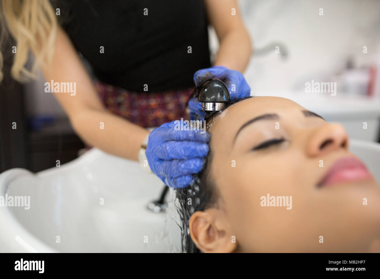 Close up portrait of relaxed woman having hair washed at hairdresser - Stock Image