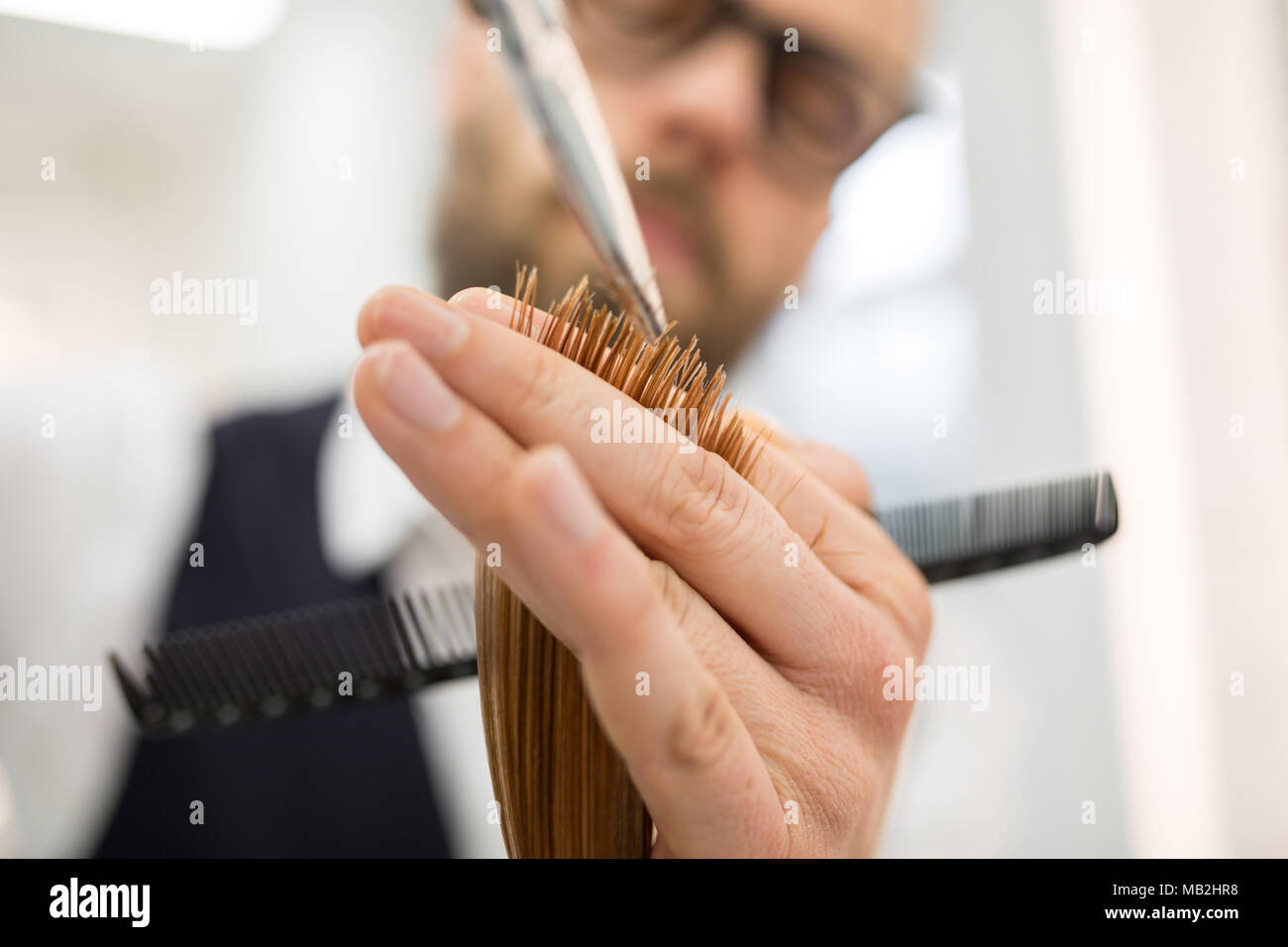 Close up portrait of hairdresser hands cutting hair ends - Stock Image