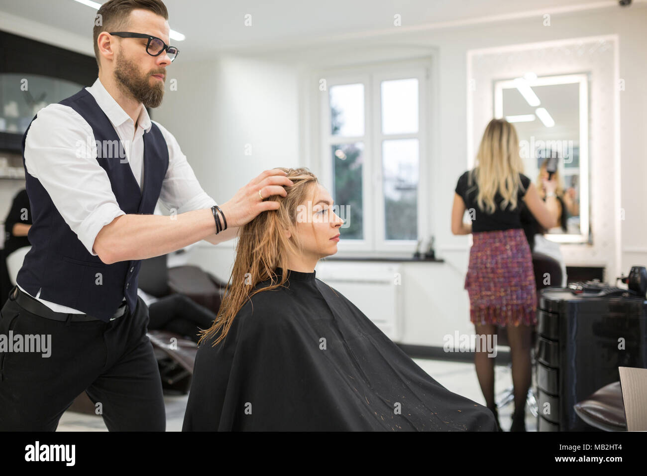 Portrait of hairdresser applying conditioner on customer hair - Stock Image