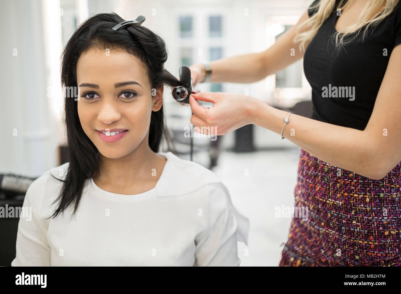 Portrait of happy woman having hair curled by hairdresser - Stock Image