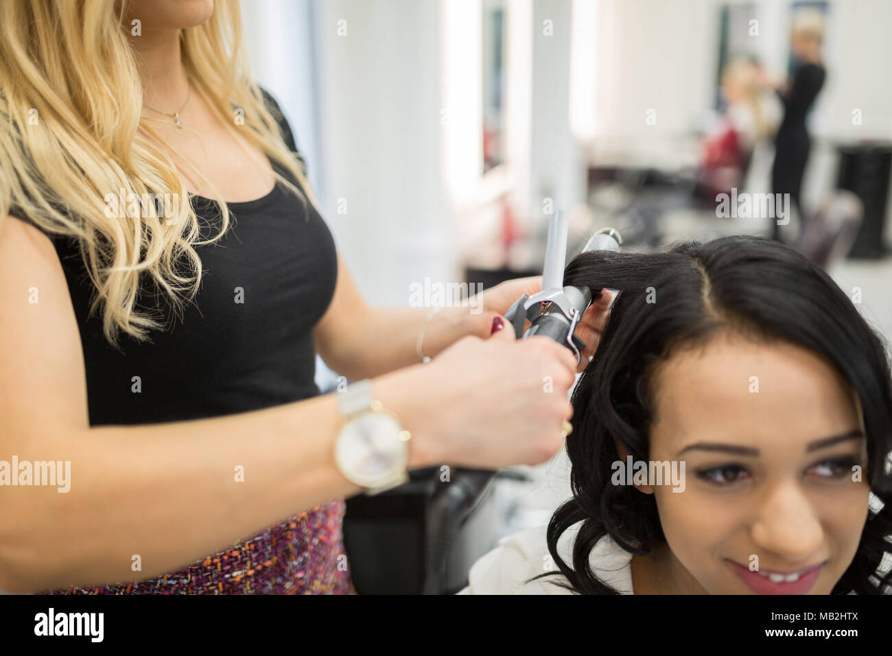 Cropped portrait of happy customer having hair curled in salon - Stock Image