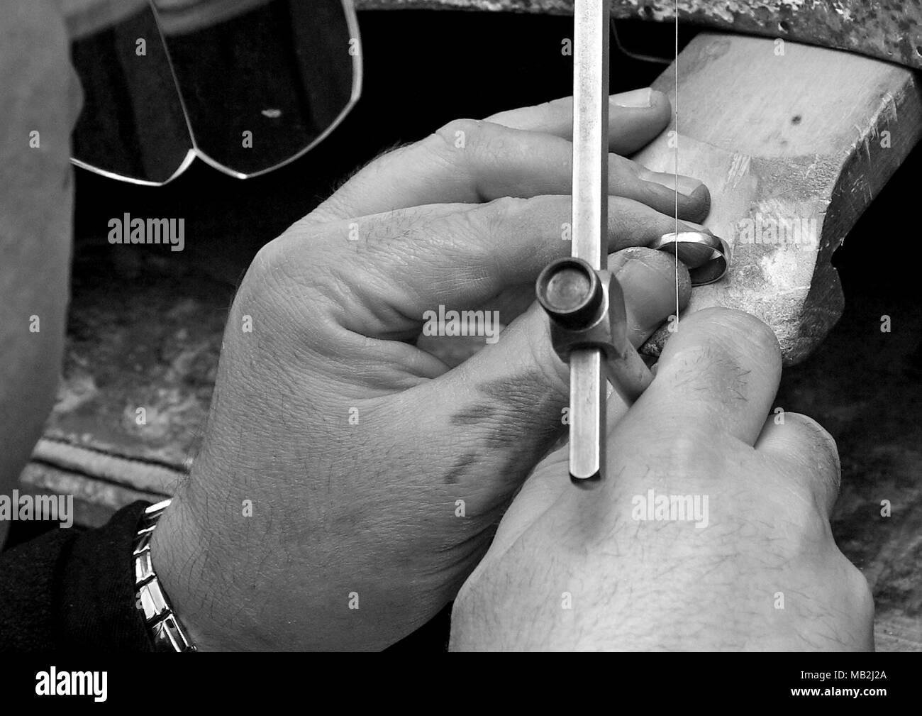 Black and white photo of the jeweler. The sawing ring. - Stock Image