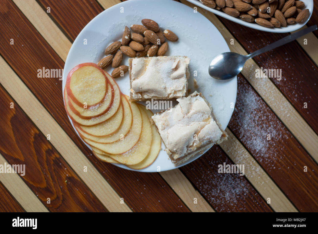 Square shape sliced omemade apple pie with kumquats and almonds on wooden background - Stock Image