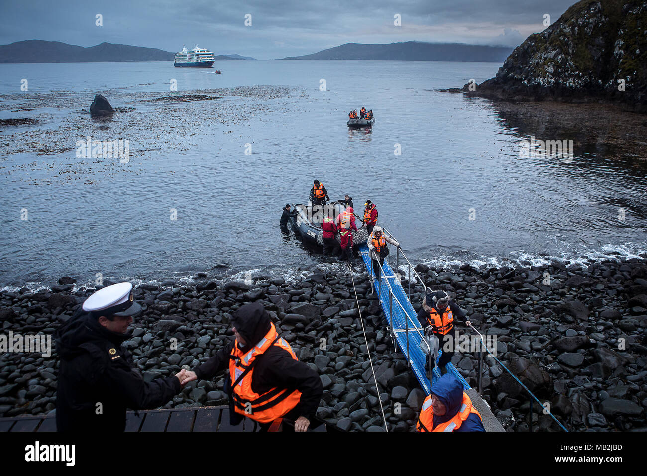 Man who works as a lighthouse keeper in the cape receives the expedition. The explorers disembark at Cape Horn, Tierra de Fuego, Patagonia, Chile - Stock Image
