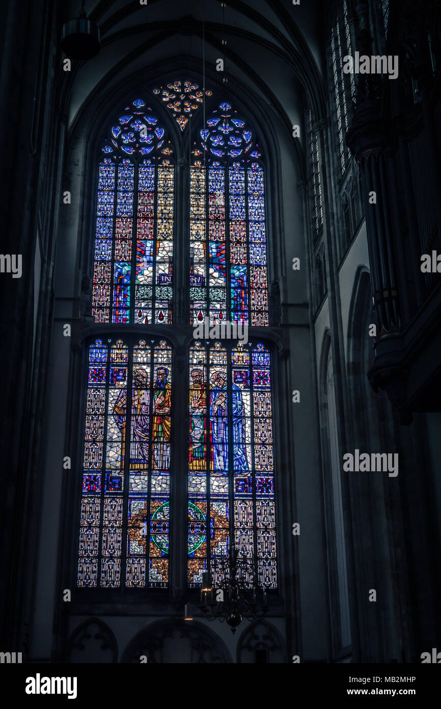 Utrecht, Netherlands - August 13, 2016: Stained glass window in the Dom Church showing the four evangelists Matthew, Mark, Luke and John under the cro Stock Photo