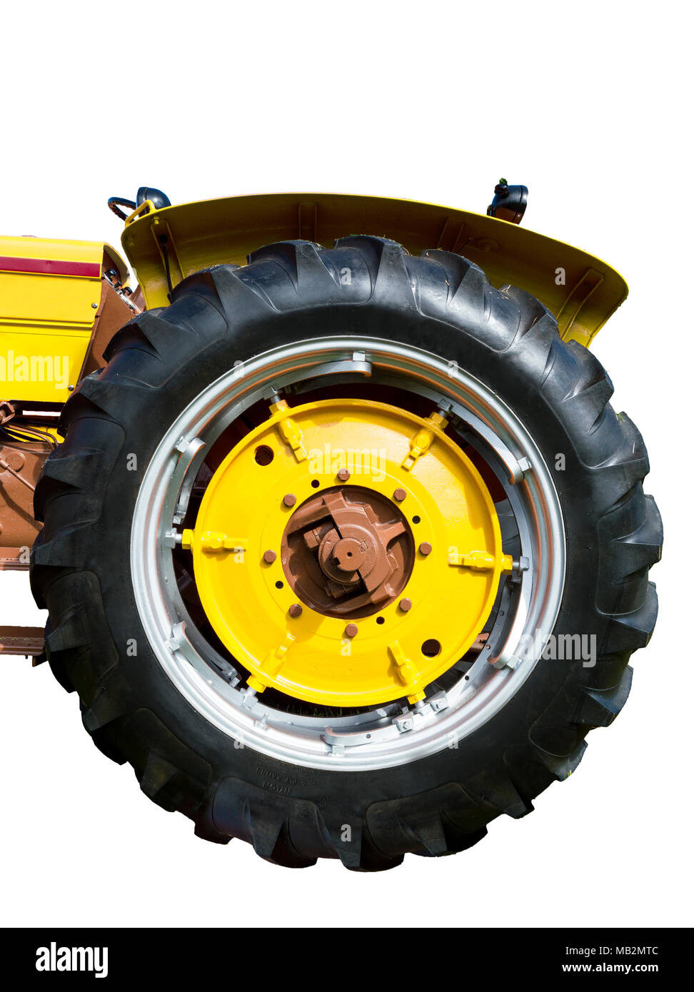 Vertical close-up shot of a big yellow tractor tire. - Stock Image