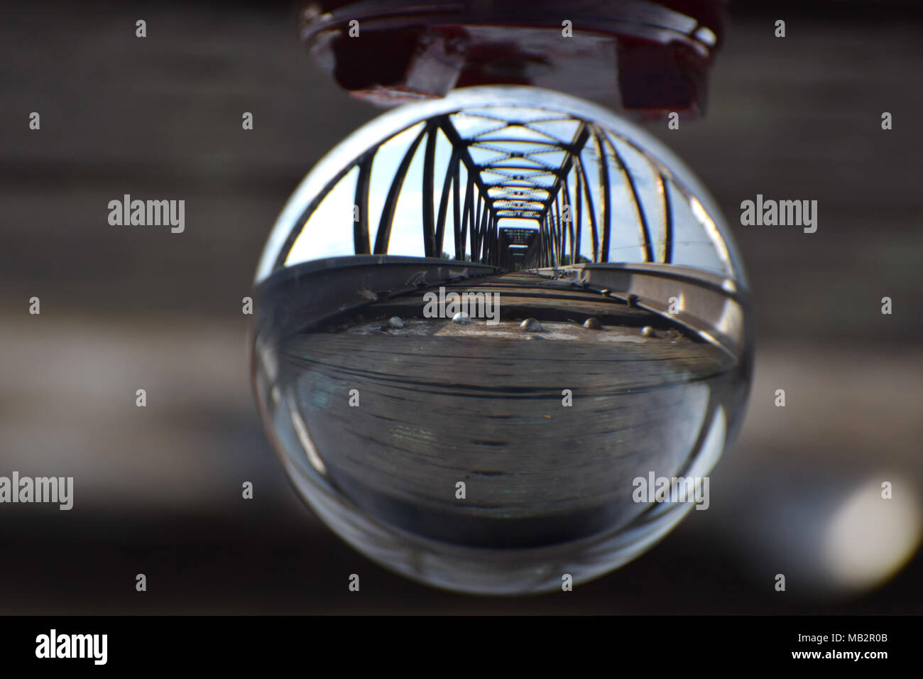 A railroad track and bridge seen through a crystal ball. A visual metaphor for vision, moving forward while staying on track and crossing bridges. - Stock Image