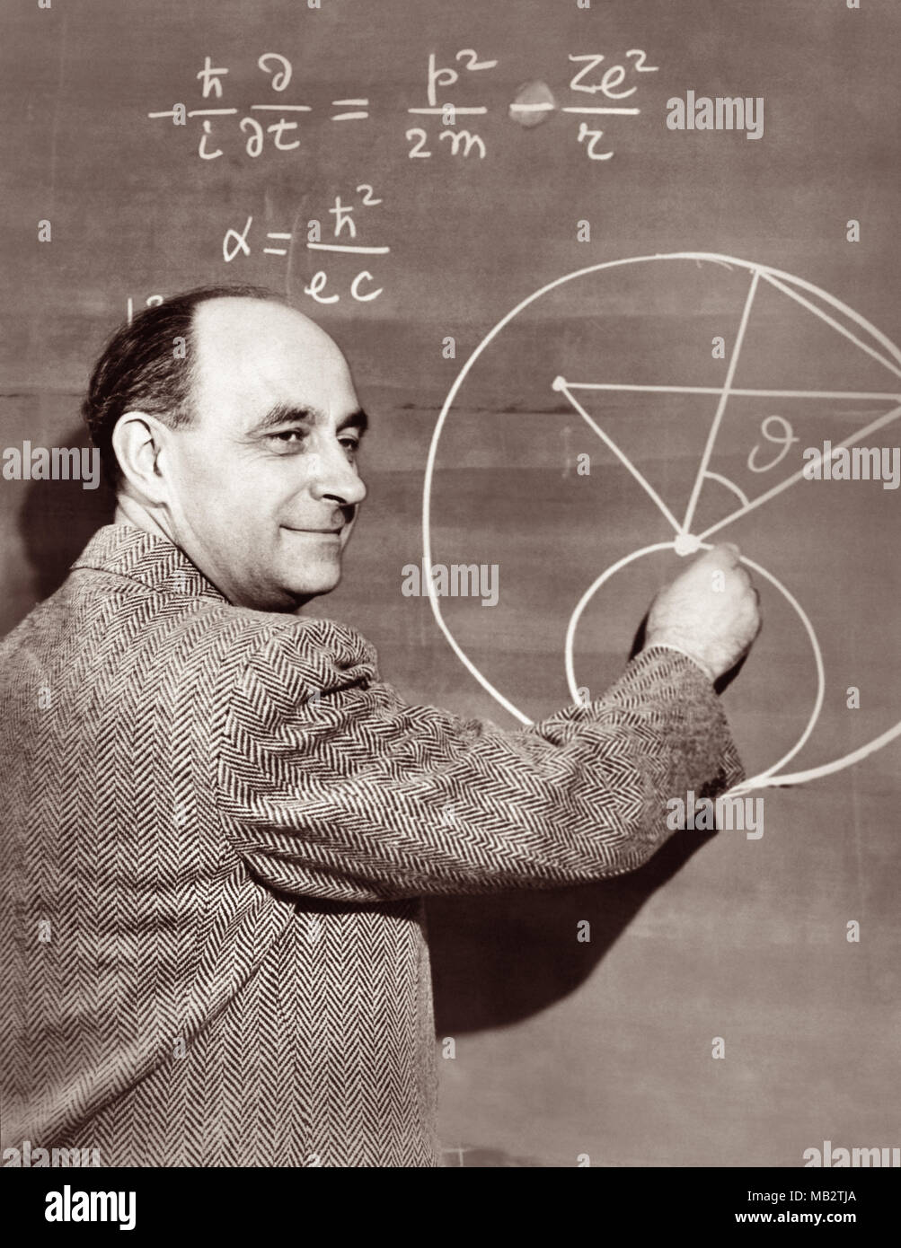 Enrico Fermi (1901–1954), Italian-American physicist and pioneer in nuclear fission, demonstates a physics equation on a chalkboard, c1950. Fermi worked on the Manhattan Project during World War II and made significant contributions to the development of quantum theory, nuclear and particle physics, and statistical mechanics. - Stock Image
