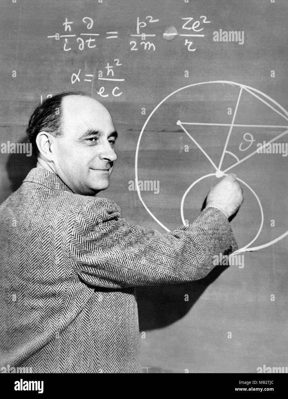 Enrico Fermi (1901–1954), Italian-American physicist and pioneer in nuclear fission, demonstates a physics equation on a chalkboard, c1950. Fermi worked on the Manhattan Project during World War II and made significant contributions to the development of quantum theory, nuclear and particle physics, and statistical mechanics. Stock Photo
