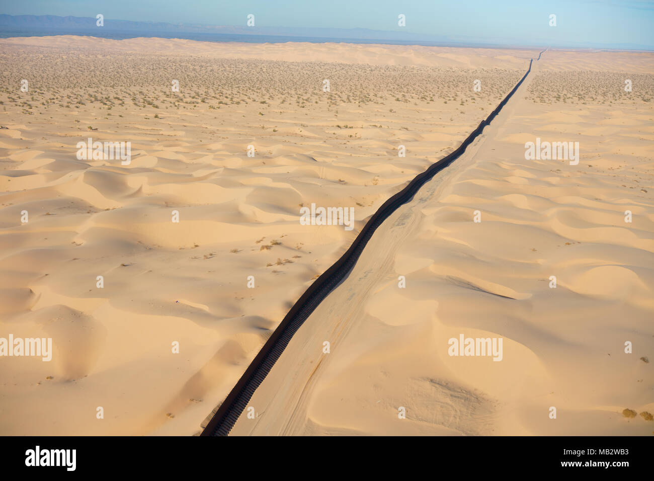 INTERNATIONAL BORDER: MEXICO - UNITED STATES (aerial view). Algodones Dunes in the Sonoran Desert, Baja California, Mexico (left of wall). - Stock Image