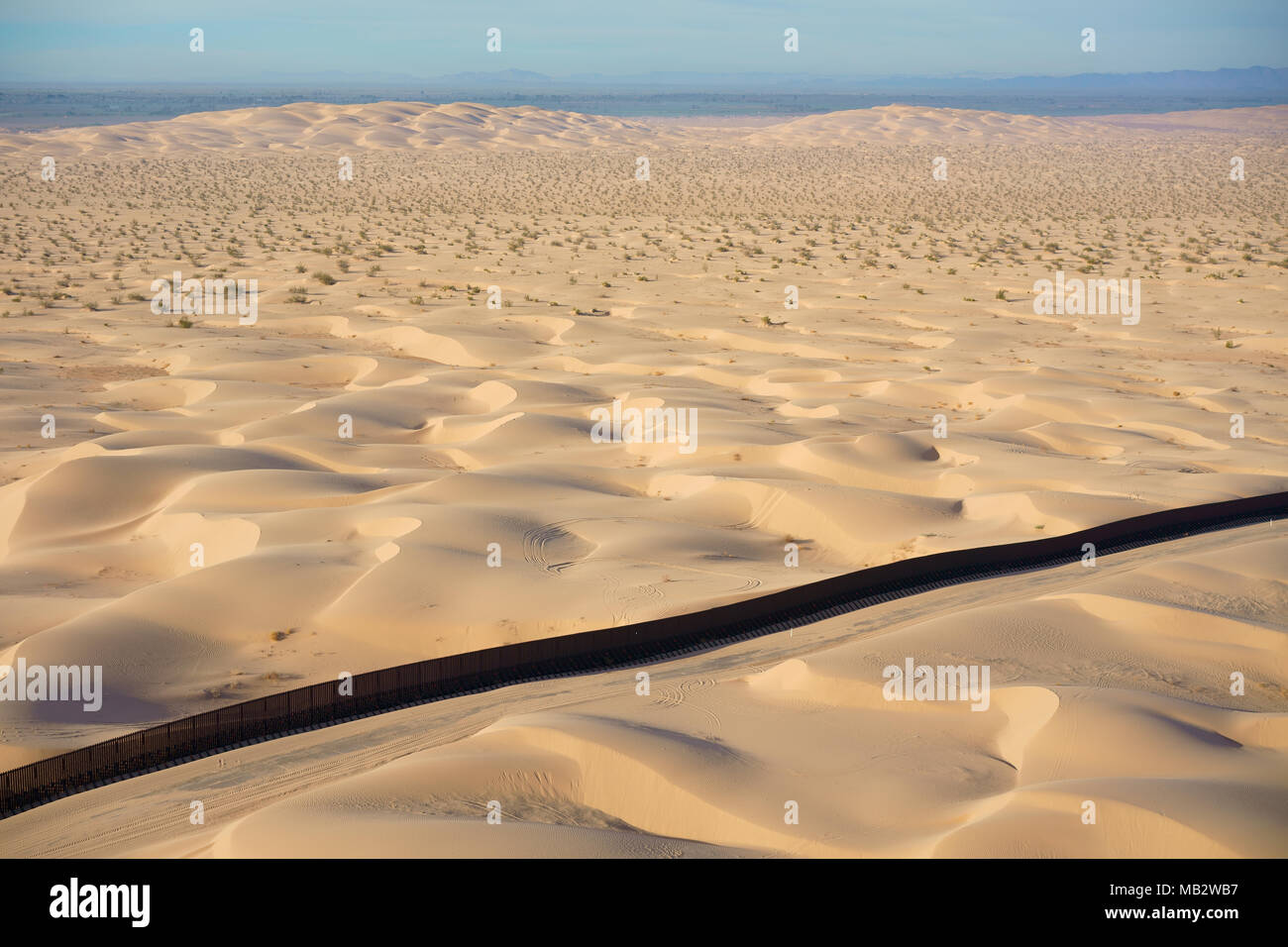 INTERNATIONAL BORDER: MEXICO - UNITED STATES (aerial view). Algodones Dunes in the Sonoran Desert, Baja California, Mexico (behind the wall). - Stock Image