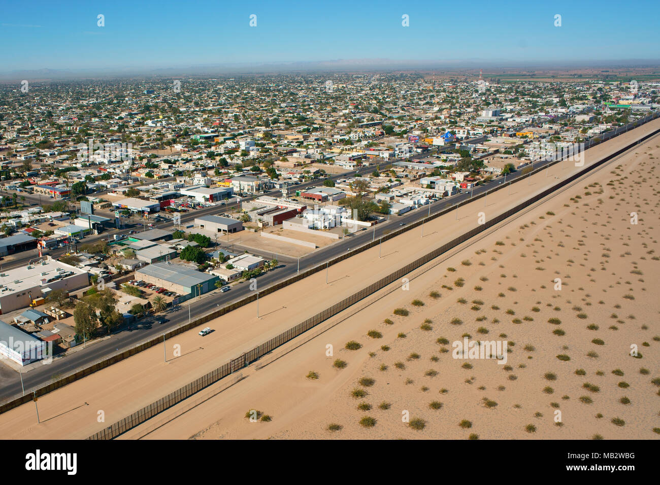 U.S. BORDER AGENT ON PATROL AT THE INTERNATIONAL BORDER OF MEXICO AND THE USA (aerial view). City of San Luis Rio Colorado in Sonora, Mexico. - Stock Image