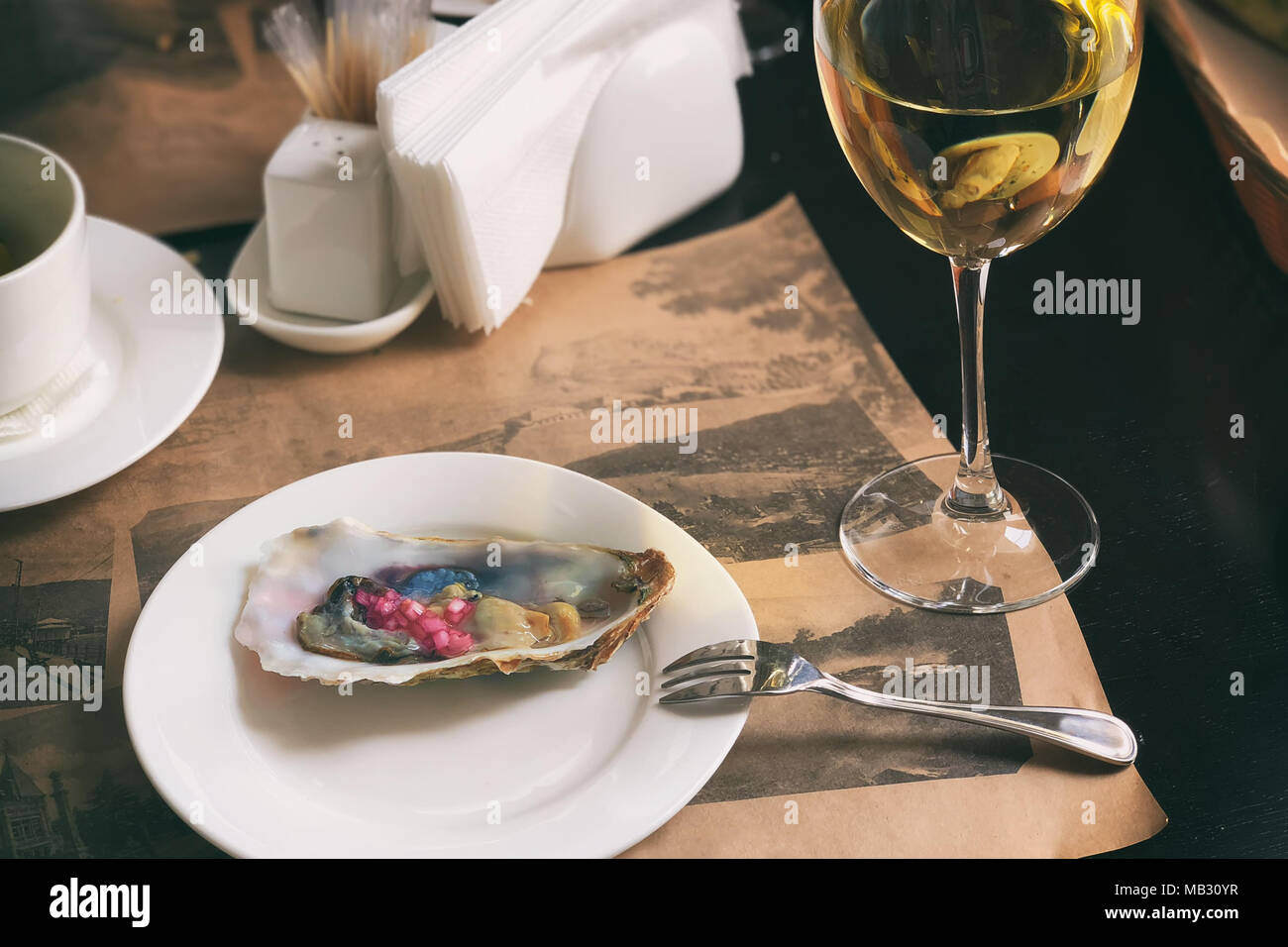 A white dish with delicious oysters is served with red Crimean onions and white wine. Serving. A horizontal frame. - Stock Image