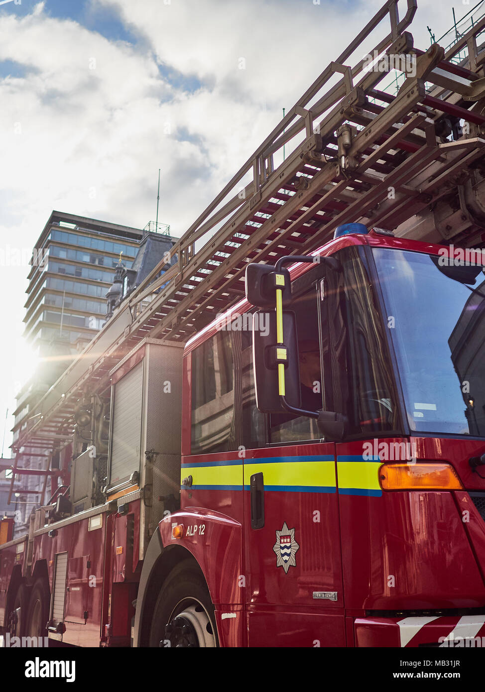 London Fire Brigade fire engine appliance pictured in bright sunshine against blue skies with sun flare across image. - Stock Image