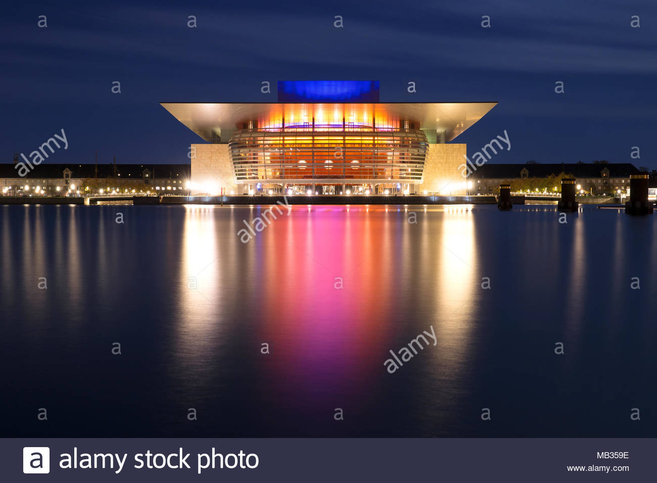 A low-light exposure of the contemporary Copenhagen Opera House, Denmark. The colours from the building at night reflect beautifully across the water. Stock Photo