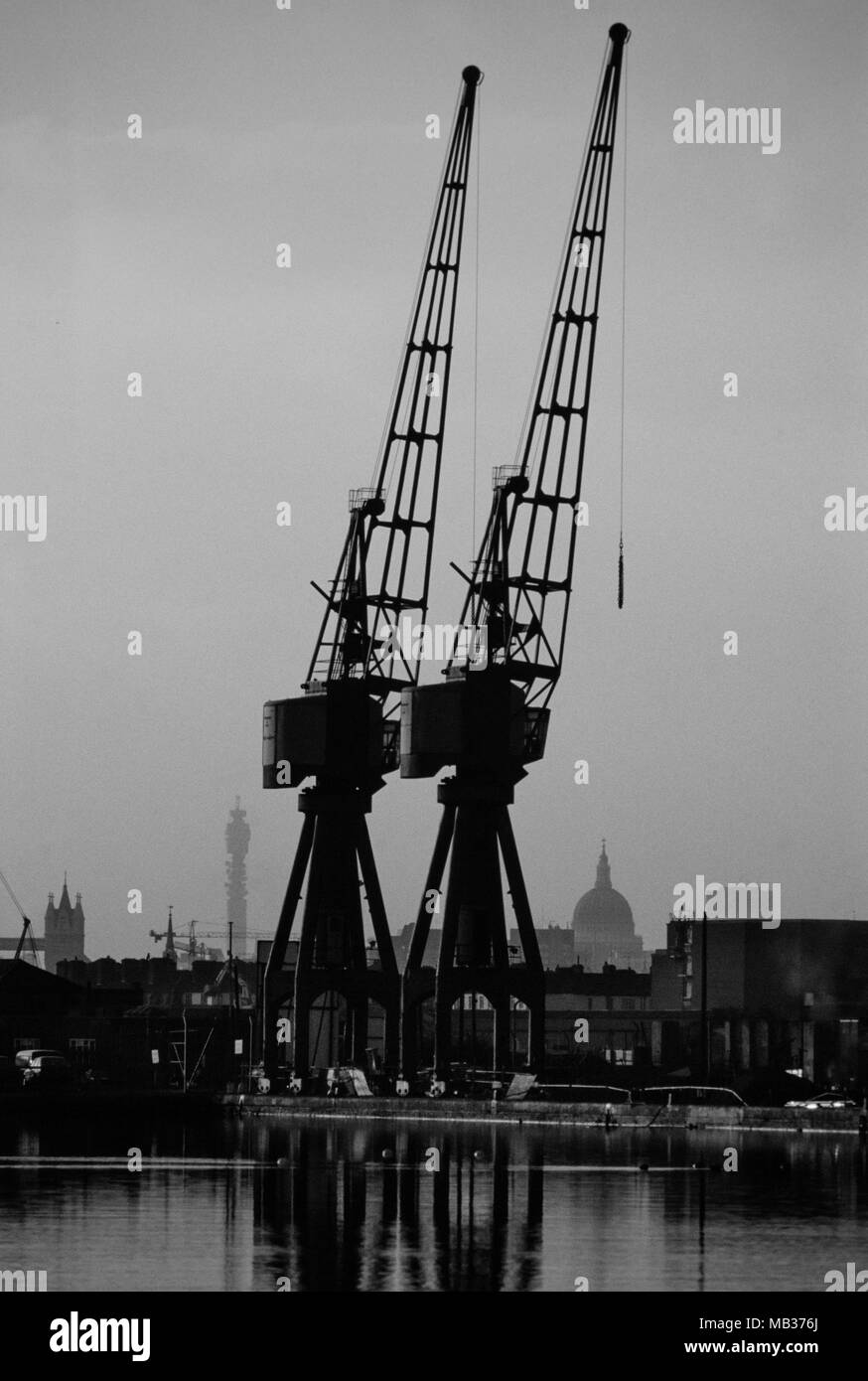 Isle Of Dogs Docklands looking toward City of London showing Cranes and St Pauls cathedral and the Post Office Tower at Dusk. 1990 - Stock Image