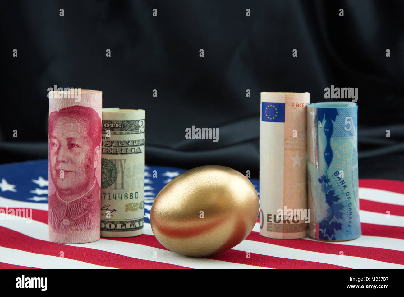 Multiple global currencies placed with gold egg on Americn flag reflect global connections underlying balanced financial portfolios, modern businesses - Stock Image