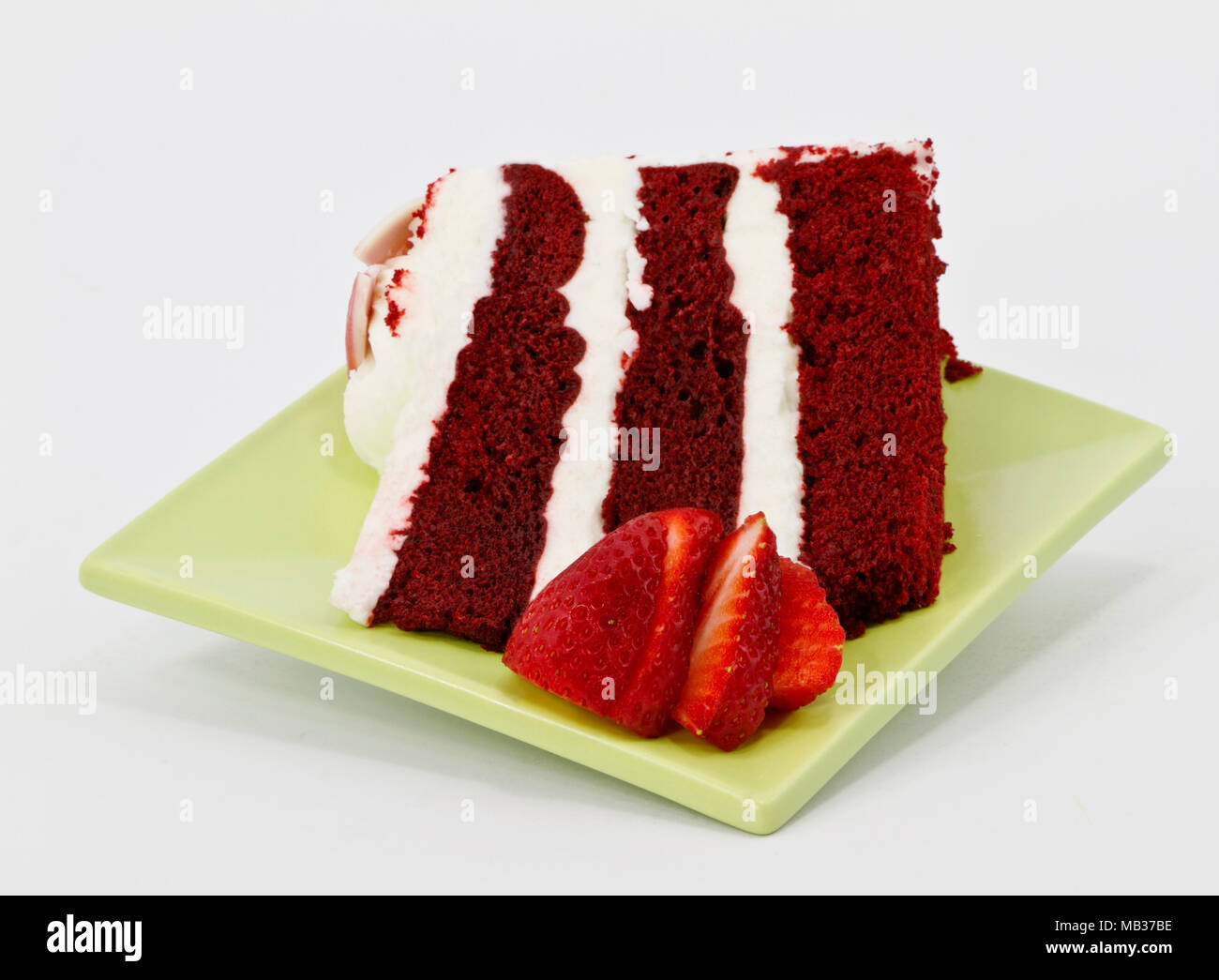 A modern square green dessert plate holds a piece of three layer red velvet cake with thick frosting garnished with sliced strawberries on white back  sc 1 st  Alamy & A modern square green dessert plate holds a piece of three layer ...